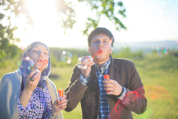 Young couple play together with bubble blower