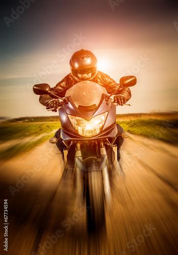 Leinwandbild Motiv Biker racing on the road
