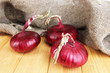 Fresh red onions on wooden table
