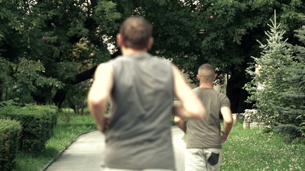 Two men jogging in the city park