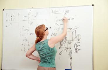 Teacher writes on blackboard
