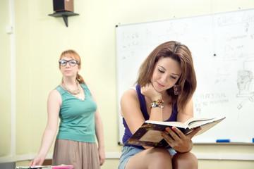beautiful schoolgirl reading a book in a classroom