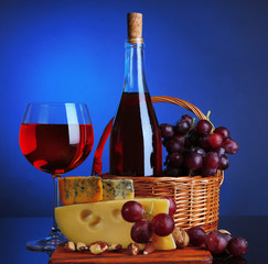 Pink wine, grapes and cheese on colorful background