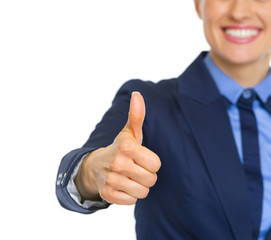 Closeup on smiling business woman showing thumbs up