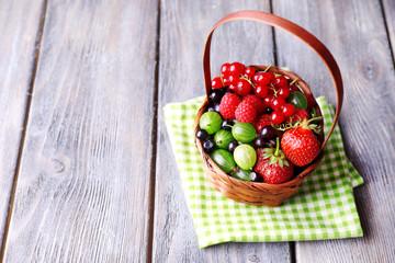 Forest berries in wicker basket, on wooden background