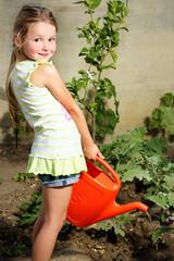 Bambina che annaffia le piante