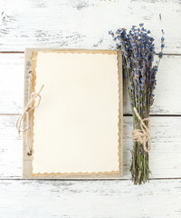 Lavender flowers and old photo album on wooden background