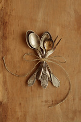 Bunch of vintage tea spoons and lemon fork tied up with bow