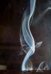 smoke of incense aromatic creating forms on a black background