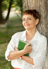 attractive woman 50 years old with a book in the park
