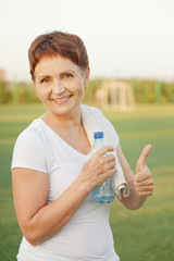 sports woman  50 years with a  bottle of water, outdoors