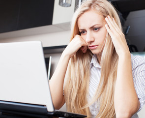 Sad woman looking at laptop