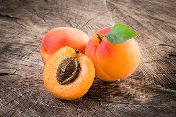 Apricots with leaves on wooden background