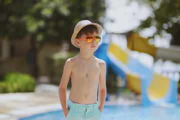 hot sunny day a little boy standing at the pool with hat and sun