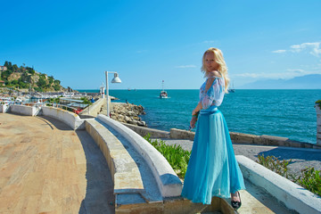 Girl at viewpoint near old harbor with yachts.