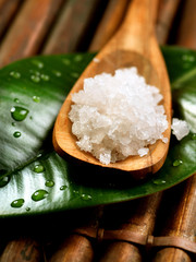 Spa salt in wooden spoon closeup. Bath salt