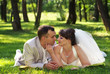Beautiful newly married couple lying on grass at park