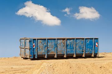 Ein grosser blauer Schuttcontainer unter blauem Himmel