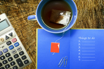 stationery, calculator, cup, notebook with things to do list