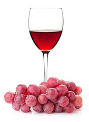 Rose wine in glass with red grape branch