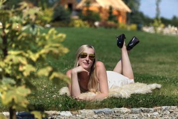 Dziewczyna, blondynka leży na trawie.