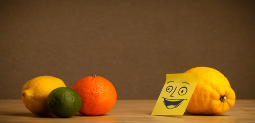 Lemon with post-it note smiling at citrus fruits