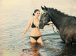 woman swimming winth  stallion in river