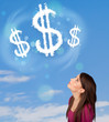Young girl pointing at dollar sign clouds on blue sky
