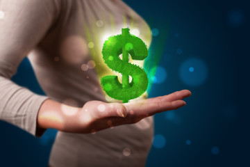 Young woman presenting green glowing dollar sign