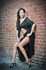 Charming young brunette woman in black staying near a brick wall