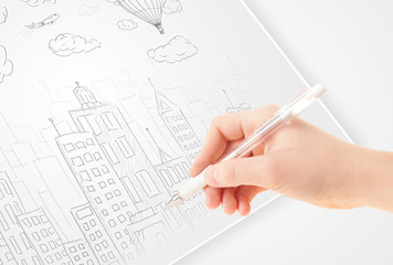A person drawing sketch of a city with balloons and clouds on a