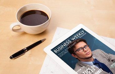 Tablet pc showing magazine on screen with a cup of coffee on a d