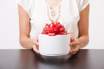 female hands and round gift box on the table