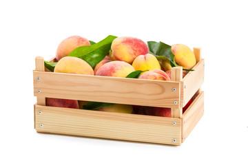 Ripe peaches in a wooden box