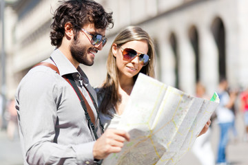 Couple of tourists reading a map in a city