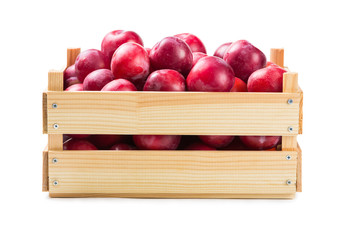 Ripe plums in a wooden box