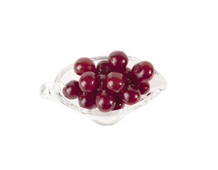 Red cherries in glass vase isolated on white