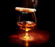 Cognac and cigar. Glass of brandy over dark background