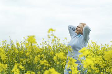 Beautiful old woman in yellow field