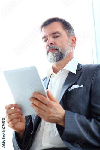 Businessman using his tablet in the office. Business man working