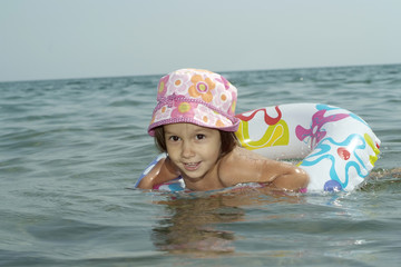 Funny little girl swims