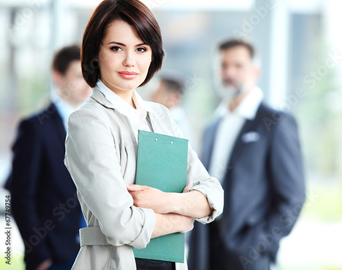 Businesswoman with her staff, people group in background