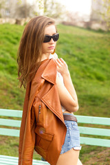 brunette girl in sunglasses with a jacket stands in the Park