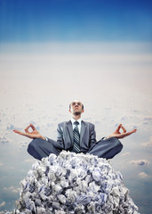 Businessman meditating on heap of documents