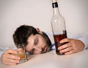 alcoholic drunk businessman sleeping wasted on work desk