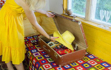 woman with yellow dress put hat old suitcase