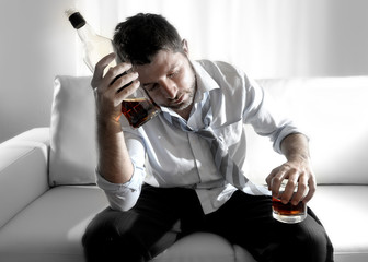 alcoholic drunk businessman wasted drinking whiskey in couch