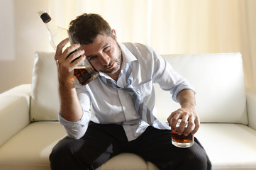 alcoholic drunk businessman and whiskey bottle in couch