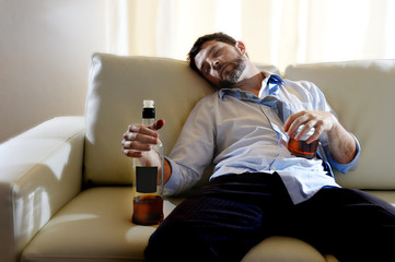 drunk businessman sleeping in couch whiskey bottle wasted