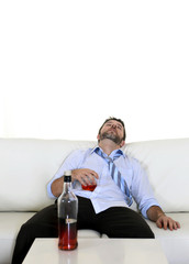 drunk businessman sleeping in couch wasted and whiskey bottle